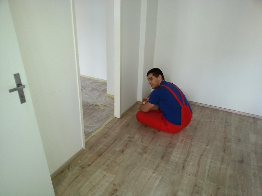 Marek oblepuje podlahové lišty